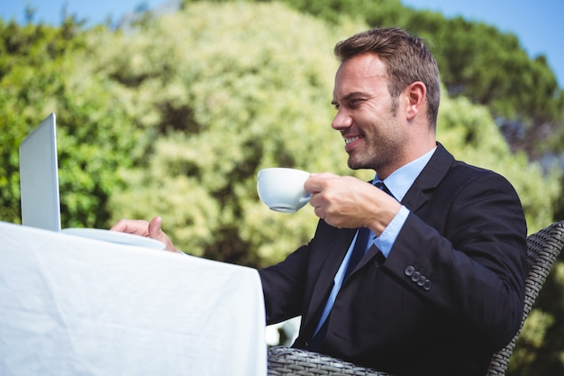 Biznesmen używa laptop i mieć kawę