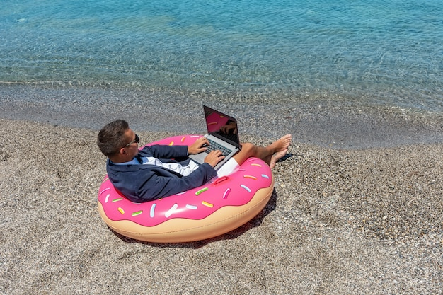 Biznesmen używa laptop na nadmuchiwanym pączku na tropikalnej plaży