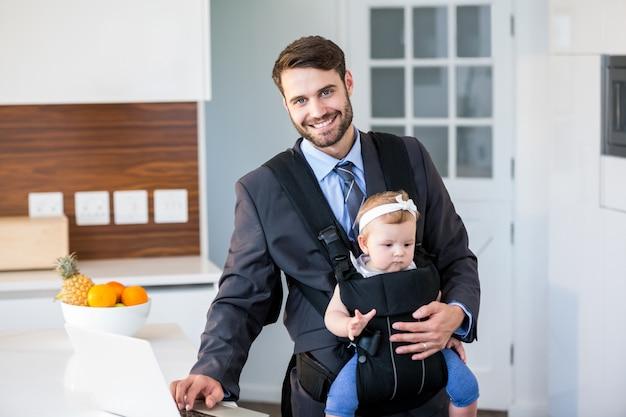 Biznesmen używa laptop podczas gdy niosący córki