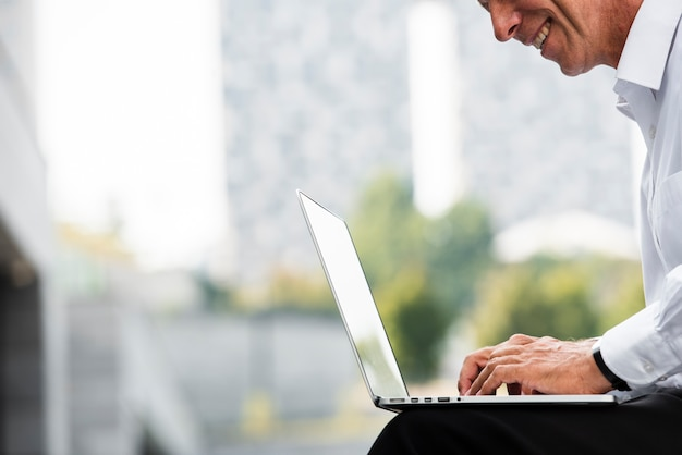 Biznesmen używa laptop podczas gdy siedzący