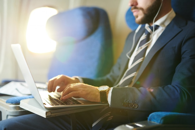 Biznesmen używa laptop w płaskim zbliżeniu