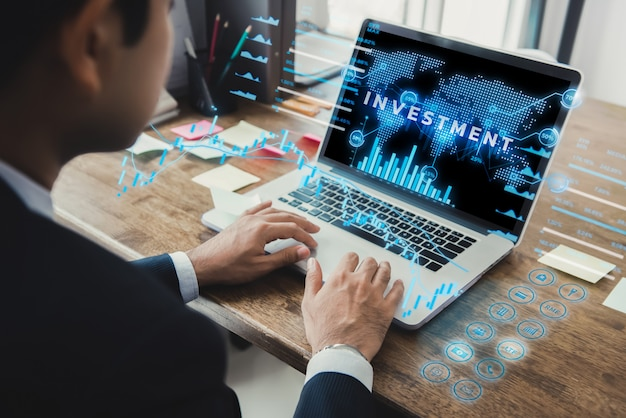 Biznesmen używa laptop z futurystycznym online pieniężnym cyfrowym dane pokazem
