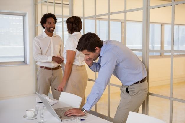 Biznesmen używa laptop z kolegami trząść ręki w tle