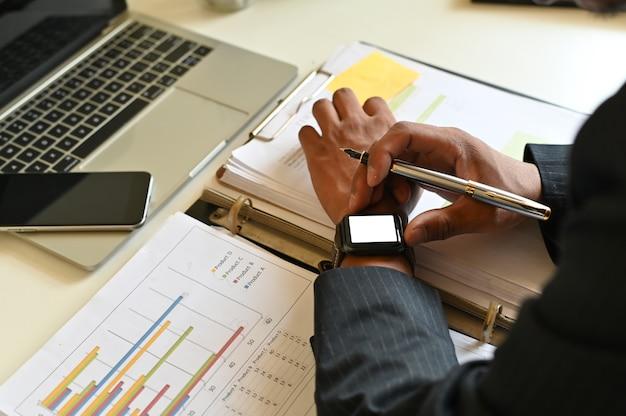 Biznesmen używa mądrze zegarka makietę na biuro stole.