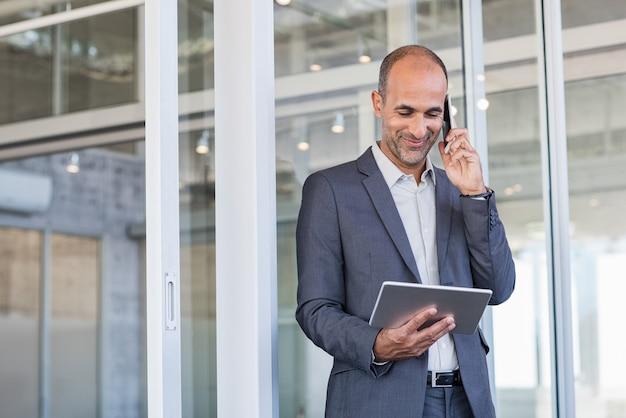 Biznesmen używa pastylkę i telefon