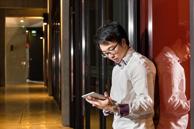 Biznesmen używa pastylkę w nowożytnym biurze