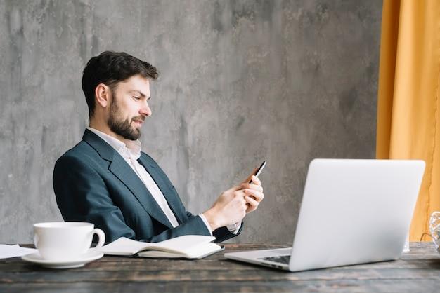 Biznesmen używa smartphone blisko laptopu
