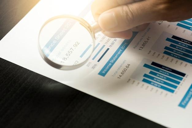 Biznesmen używa szkła powiększającego do analizy danych finansowych i znajduje najlepszą firmę z giełdy. inwestor wartości