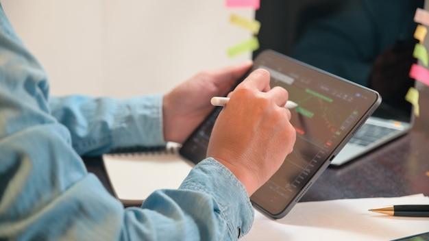 Biznesmen używa tabletu do analizowania wykresów giełdowych, wykresu zysków, finansów i bankowości i zleca sprzedaż lub kupno
