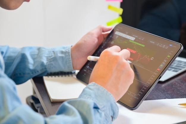 Biznesmen używa tabletu do analizowania wykresów giełdowych, wykresu zysków, finansów i bankowości i zleca sprzedaż lub kupno.