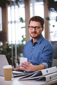 Biznesmen używa telefon komórkowego podczas gdy pracujący na laptopie przy biurem