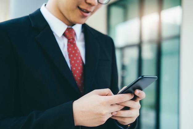 Biznesmen używa telefon komórkowy app texting na zewnątrz biura.