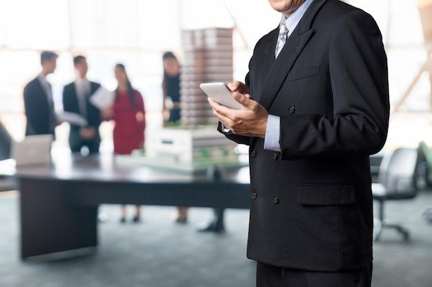 Biznesmen używać bezprzewodowego urządzenia mobilnego smartphone w sali konferencyjnej