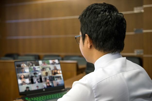 Biznesmen używać komputera do spotkania zespołu z programem do rozmów wideo.
