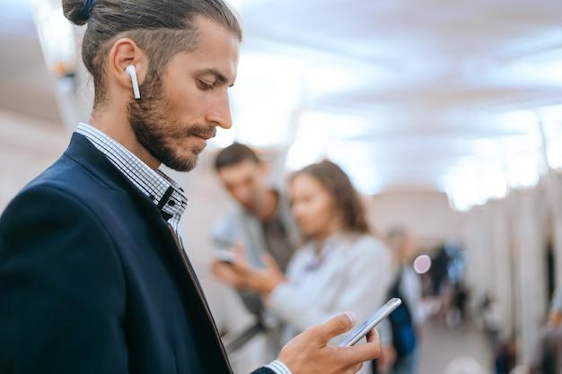 Biznesmen, używając swojego smartfona w metrze.