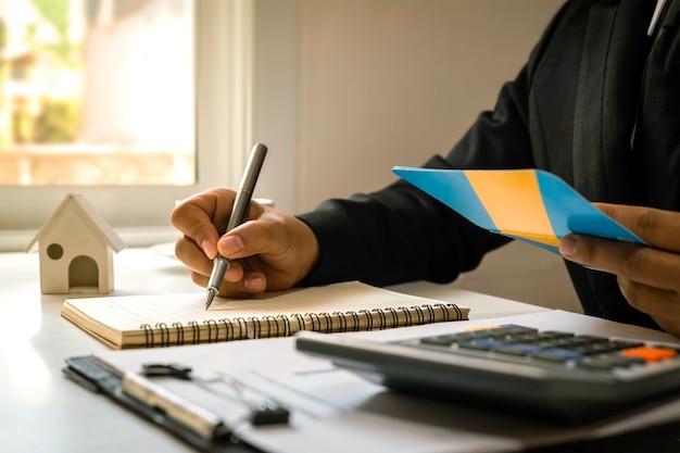 Biznesmen używający długopisu do pisania raportów finansowych sporządzanie sprawozdań finansowych