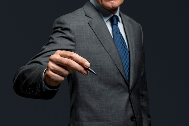 Biznesmen używający długopisu i podpisujący się na niewidzialnym ekranie