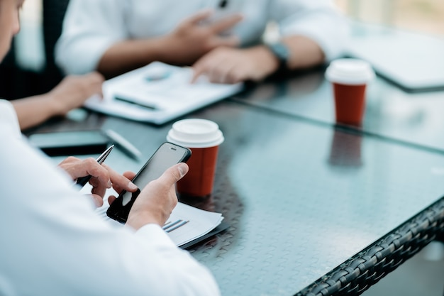 Biznesmen używający swojego smartfona do analizy wykresu finansowego