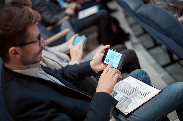 Biznesmen używający swojego smartfona siedząc w sali konferencyjnej