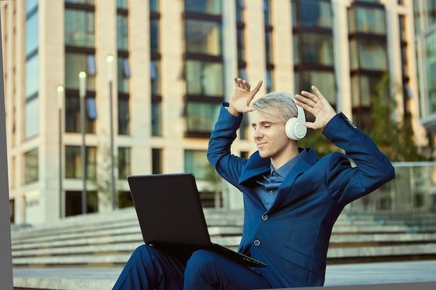 Biznesmen w bezprzewodowych słuchawkach i laptopie siedzi w pobliżu centrum biznesowego