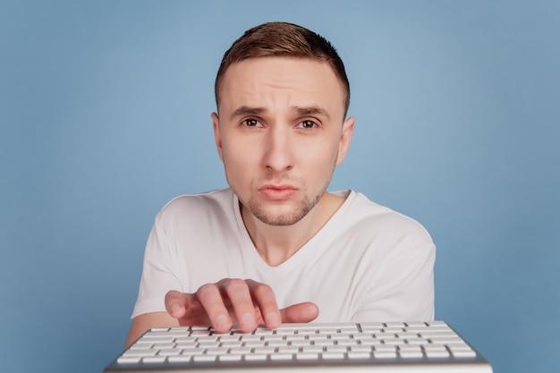 Biznesmen w białej koszulce piszący na klawiaturze komputera praca e-mailowa skoncentrowana na białym tle na niebieskim tle