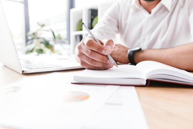 Biznesmen w białej koszuli siedzi przy stole i zapisując informacje ołówkiem w notesie, pracując w jasnym pomieszczeniu biurowym