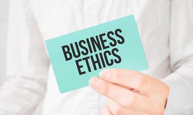 Biznesmen w białej koszuli trzyma zieloną kartę z tekstem etyka biznesowa