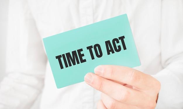 Biznesmen w białej koszuli, trzymając zieloną kartę z tekstem czas na podjęcie działań
