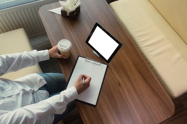 Biznesmen w białej koszuli z cyfrowym tabletem w rękach podpisuje umowę w biurze. stanowisko pracy z filiżanką kawy i dokumentem z długopisem na drewnianym stole.