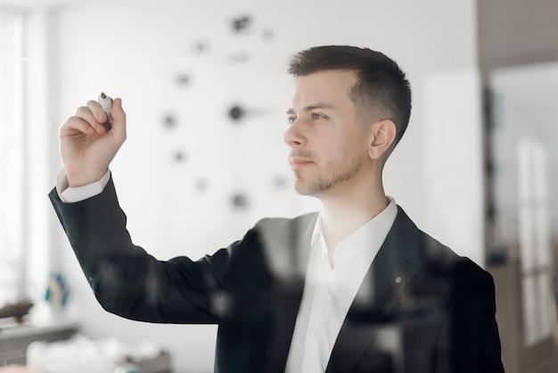 Biznesmen w biurowej rysunek mapie na szklanej ścianie