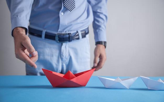 Biznesmen w biurze. czerwona papierowa łódź origami z białymi łodziami. biznes, przywództwo