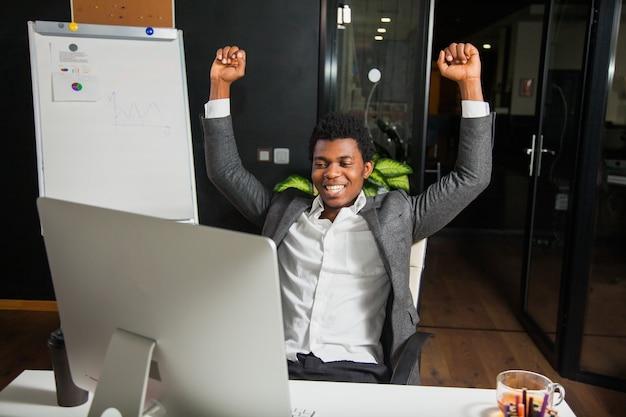 Biznesmen w biurze, gest sukcesu, cel osiągnięty, szczęśliwy człowiek
