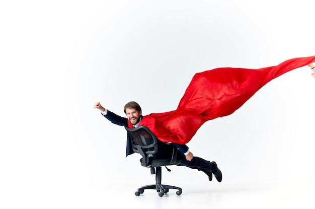 Biznesmen w biurze kierownika supermana w czerwonym płaszczu