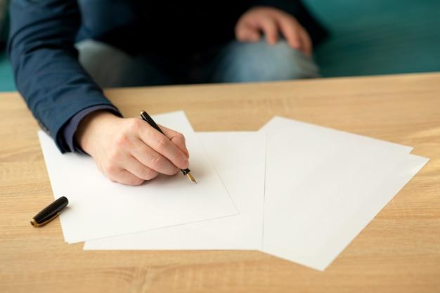 Biznesmen w biurze pisze list lub podpisuje dokument na kartce białego papieru wiecznym piórem ze stalówką. zbliżenie dłoni