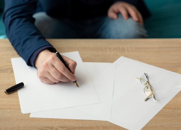 Biznesmen w biurze pisze list lub podpisuje dokument na kartce białego papieru wiecznym piórem ze stalówką. zbliżenie na ręce biznesmena w garniturze