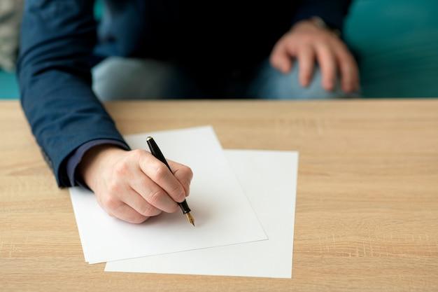 Biznesmen w biurze pisze list lub podpisuje dokument na kartce białego papieru wiecznym piórem ze stalówką.