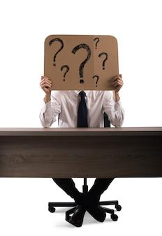 Biznesmen w biurze posiada karton ze znakami zapytania