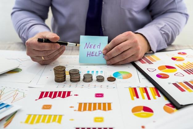 Biznesmen w biurze pracuje i analizuje zyski firmy za pomocą wykresów i dokumentów za pomocą monet. analiza biznesowa i koncepcja strategii