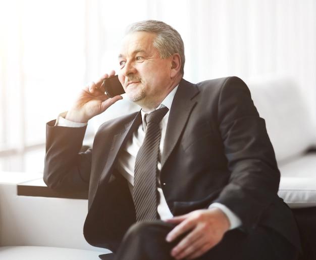 Biznesmen w biurze siedzi na kanapie rozmawia przez telefon i wygląda przez okno