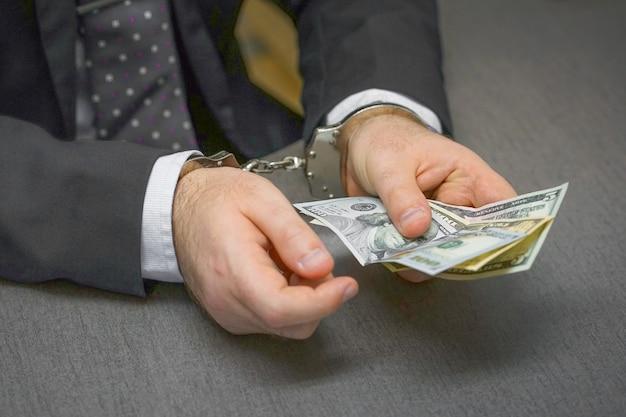 Biznesmen w biurze w kajdankach trzymając łapówkę. selektywne skupienie
