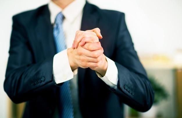 Biznesmen w biurze z rękami złożonymi. chęć przyjaźni i współpracy.