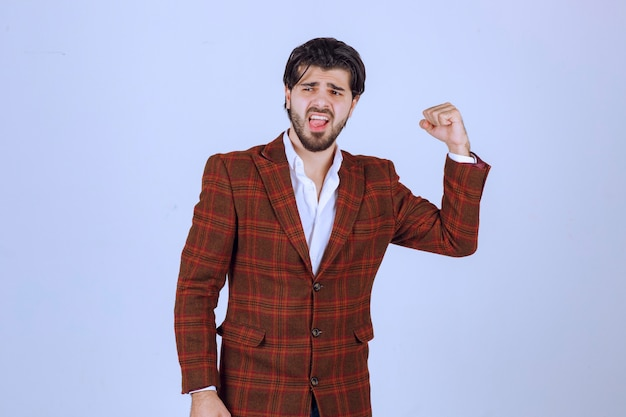 Biznesmen w brązowej kurtce, pokazując pięści i podkreślając jego sukces i siłę.