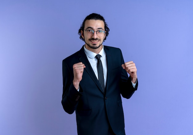 Biznesmen w czarnym garniturze i okularach patrząc do przodu, uśmiechnięty wesoło, zaciskając pięści szczęśliwy i podekscytowany, stojąc nad niebieską ścianą