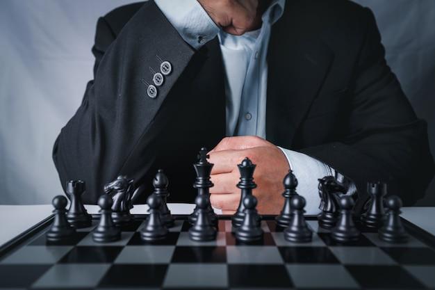 Biznesmen w czarnym garniturze siedzi i zespół kontrolny z przodu do pozycji sukcesu w grze biznesowej konkurencji