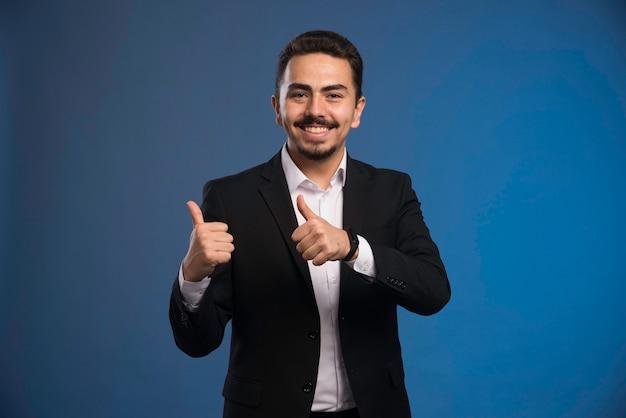 Biznesmen w czarnym garniturze sprawia, że kciuki do góry.