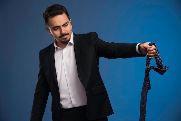 Biznesmen w czarnym garniturze trzyma krawat.