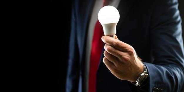 Biznesmen w czarnym garniturze trzyma w dłoni żarówkę oświetloną na czarnym tle z kopią przestrzeni. pomysł na rozwój biznesu pomysł na biznes.