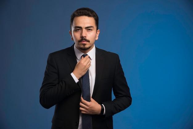 Biznesmen w czarnym garniturze z krawatem.