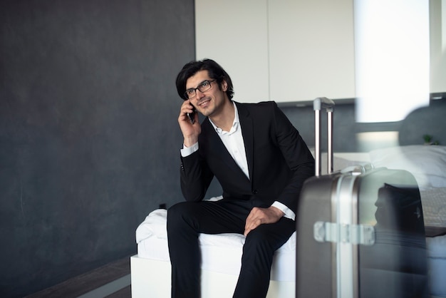Biznesmen w domu rozmawia przez telefon gotowy do podróży