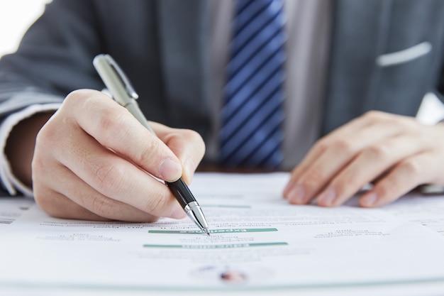 Biznesmen w eleganckim garniturze na spotkaniu biznesowym podpisującym umowy w biurze